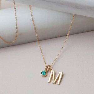 This emerald initial necklace in yellow gold is a favorite piece of emerald jewelry - a perfect May birthstone jewelry gift.