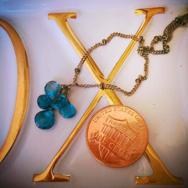 elsa style birthstone necklace next to a penny